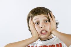 El hacer muecas temeroso del muchacho en blanco Imágenes de archivo libres de regalías