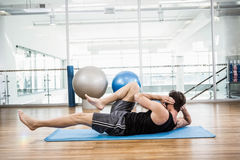 El hacer muscular del hombre abdominal en la estera Imagen de archivo libre de regalías
