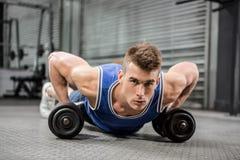 El hacer muscular del hombre empuja hacia arriba con pesas de gimnasia Fotos de archivo