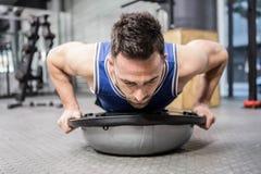 El hacer muscular del hombre empuja hacia arriba en bola del bosu Imagenes de archivo
