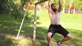 El hacer muscular joven barbudo del hombre levanta exercisings en una barra transversal de la meta del fútbol cantidad lenta de 4 almacen de video