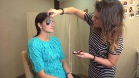 El hacer profesional del artista de maquillaje compensa el modelo hermoso Apacible compense a la chica joven Demostración de mode almacen de metraje de vídeo