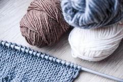 El hacer punto con lanas grises y lanas grises y blancas marrones Foto de archivo