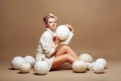 El hacer punto. Costura. Mujer en ropa hecha punto blanco con el bulto de ovillos mullidos del hilado Fotos de archivo libres de regalías