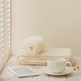 El hacer punto, eBook y una taza en un fondo de madera ligero cerca de un w Fotografía de archivo libre de regalías