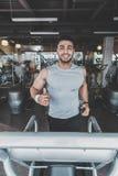 El hacer saliente del hombre cardiio en gimnasio moderno Foto de archivo libre de regalías