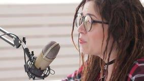 El hacer un podcast y concepto de radio Mujer joven del anfitrión de radio en el estudio delante de un micrófono almacen de metraje de vídeo