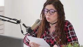 El hacer un podcast y concepto de radio Mujer joven del anfitri?n de radio en el estudio delante de un micr?fono almacen de video