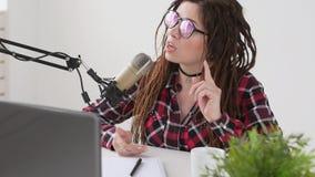 El hacer un podcast y concepto de radio Mujer joven del anfitri?n de radio en el estudio delante de un micr?fono metrajes