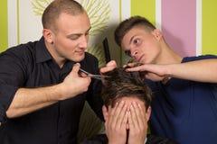 El hairstyling de los hombres y el haircutting con las podadoras de pelo y scissor imagenes de archivo