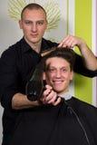 El hairstyling de los hombres y el haircutting con las podadoras de pelo y scissor foto de archivo libre de regalías