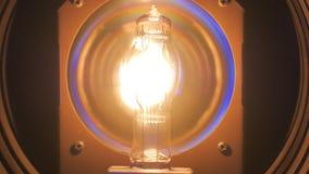 El halógeno que es la lámpara profesional se enciende para arriba de la oscuridad, iluminación brillante, primer almacen de metraje de vídeo