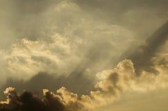 El haz de voladura de las nubes en el cielo de oro en la puesta del sol fotografía de archivo