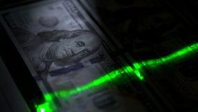 El haz verde se mueve lentamente a lo largo de la denominación de $ 100 almacen de video