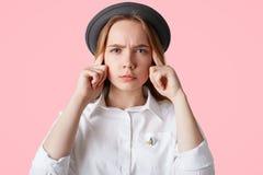 El Headshot de la hembra seria con la expresión pensativa, guarda los fingeres en los templos, lleva el sombrero de moda y la cam Foto de archivo