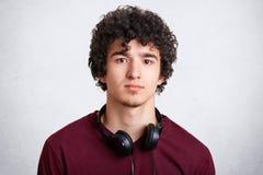 El Headshot del adolescente masculino rizado tiene auriculares en cuello, disfruta de música que escucha durante tiempo libre, ll Imágenes de archivo libres de regalías