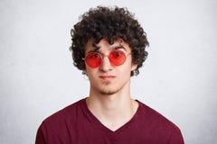 El Headshot del varón joven barbudo elegante fresco con el pelo rizado, lleva los vidrios redondos rojos de moda, alista para ten Fotos de archivo libres de regalías