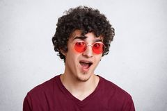 El Headshot del varón rizado sorprendente en gafas de sol de moda, lleva la ropa casual, mantiene la boca abierta, siendo aturdid Fotos de archivo