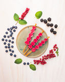 El helado de las bayas hace estallar con la pasa roja, zarzamoras, arándanos y la hierbabuena se va, componiendo en el fondo de m Imagen de archivo libre de regalías