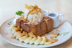 El helado de vainilla en la miel tostó el pan con el plátano imagen de archivo