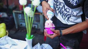 El helado en la calle Asia, el vendedor añade la crema azotada al helado almacen de video