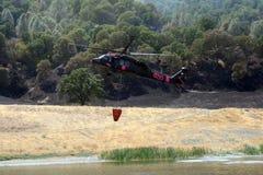 El helicóptero contraincendios rellena el cubo de agua Fotografía de archivo libre de regalías
