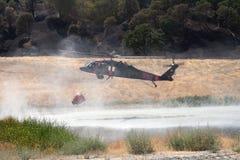 El helicóptero contraincendios rellena el cubo de agua Fotos de archivo