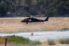 El helicóptero contraincendios rellena el cubo de agua Imagen de archivo