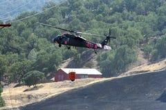 El helicóptero contraincendios vuela sobre tierra quemada Imagenes de archivo