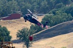 El helicóptero contraincendios vuela sobre tierra quemada Imágenes de archivo libres de regalías