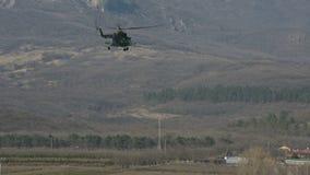 El helicóptero militar de la fuerza aérea rusa vuela en el cielo claro azul contra la perspectiva de las montañas del metrajes