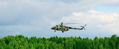 El helicóptero vuela sobre el bosque contra el cielo y las nubes fotografía de archivo libre de regalías
