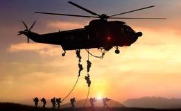 El helic?ptero del equipo del asalto de la fuerza especial cae durante puesta del sol foto de archivo libre de regalías