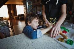 El hermano de dos muchachos prepara la pasta para las galletas La figura del más viejo muchacho no es completamente visible imagen de archivo libre de regalías