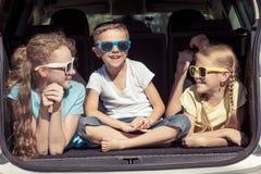 El hermano feliz y sus dos hermanas se están sentando en el coche en imágenes de archivo libres de regalías