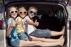 El hermano feliz y sus dos hermanas se están sentando en el coche en fotografía de archivo