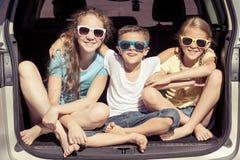 El hermano feliz y sus dos hermanas se están sentando en el coche en imagenes de archivo