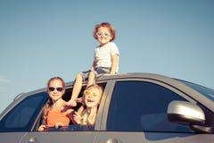 El hermano feliz y sus dos hermanas se están sentando en el coche fotos de archivo libres de regalías