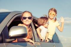 El hermano feliz y sus dos hermanas se están sentando en el coche Foto de archivo