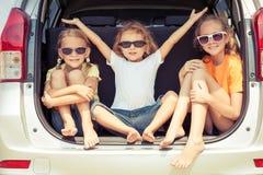 El hermano feliz y sus dos hermanas se están sentando en el coche imágenes de archivo libres de regalías