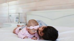 El hermano lindo juega con su pequeña hermana en una cama en casa almacen de metraje de vídeo
