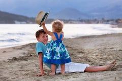 El hermano mayor feliz está jugando con su hermana más joven Foto de archivo