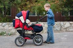 El hermano rueda al bebé. Fotografía de archivo libre de regalías