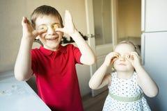 El hermano y la hermana divertidos se cierran los ojos con el caramelo como los vidrios fotos de archivo