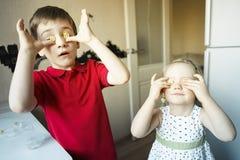 El hermano y la hermana divertidos se cierran los ojos con el caramelo como los vidrios imágenes de archivo libres de regalías