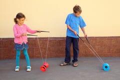 El hermano y la hermana juegan con el juguete del yoyo Imágenes de archivo libres de regalías