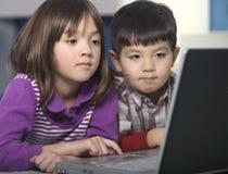 El hermano y la hermana utilizan la computadora portátil. Foto de archivo libre de regalías