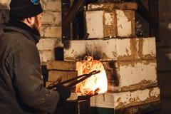 El herrero barbudo del hombre sale un billete candente del horno fotografía de archivo libre de regalías