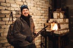 El herrero barbudo del hombre sale un billete candente del horno imagen de archivo libre de regalías