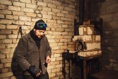 El herrero barbudo enciende el fuego con el firesteel y el pedernal foto de archivo libre de regalías